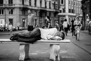 A men sleeping on the bench downtown black and white photo